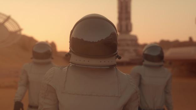 Три космонавта в скафандрах уверенно идут по марсу