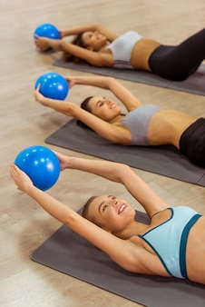 Three attractive sport girls smiling while working out.