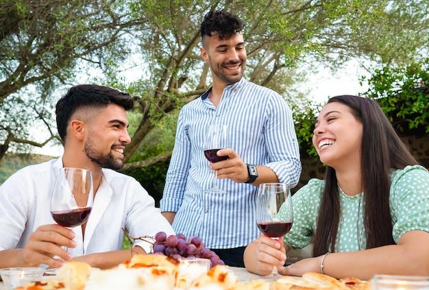 Три привлекательных молодых счастливых человека празднуют на открытом воздухе с бокалами для красного вина