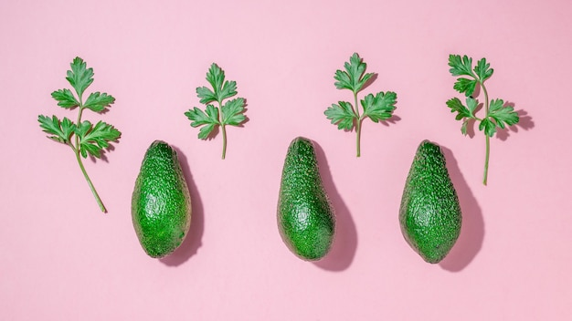 Three avocados and parsley leaves in bright light on a pink background. delicious tropical vegetable. flat lay.