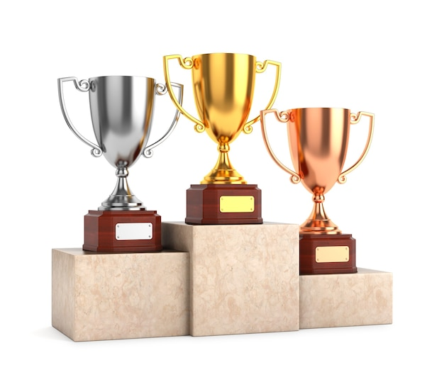 Three award goblet trophies: gold, silver and bronze trophy cups on marble pedestal isolated on white background.