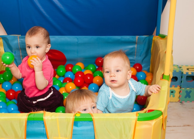 Three babies playing with multicolored small balls inside the playpen