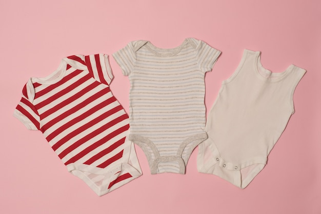 Three baby bodysuit on a pink background. clothes concept
