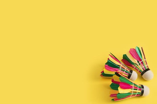 복사 공간 노란색 배경에 여러 가지 빛깔의 깃털을 가진 3 개의 배드민턴 셔틀콕