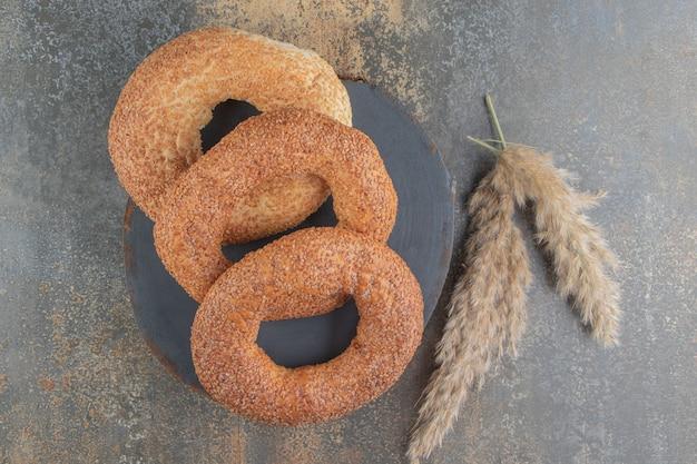 Tre bagel accanto a gambi di erba piuma su tavola di legno sul tavolo di marmo