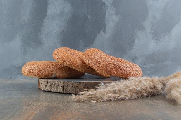 Tre bagel accanto a steli su tavola di legno