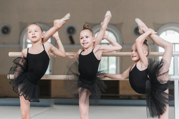 Three ballerina girls stretching their legs on barre in dance studio