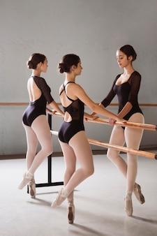 Три балерины в пуантах и трико репетируют