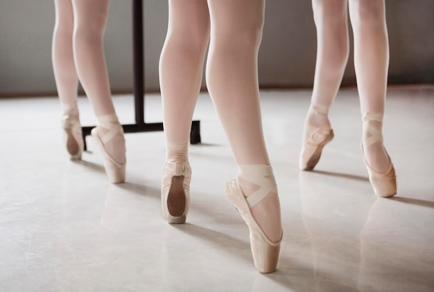 Three ballerinas in pointe shoes rehearsing