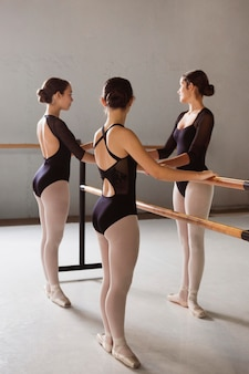 Three ballerinas rehearsing in pointe shoes