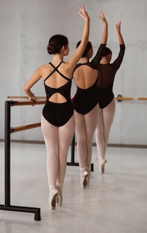 Three ballerinas rehearsing together while wearing leotards