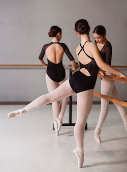 Three ballerinas rehearsing while wearing leotards