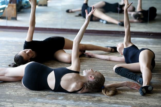 Три балерины на полу во время репетиции