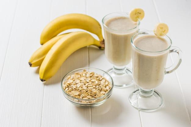 Три банана и стакана овсяных хлопьев и банановых смузи на белом столе. вегетарианский смузи. спортивное питание.