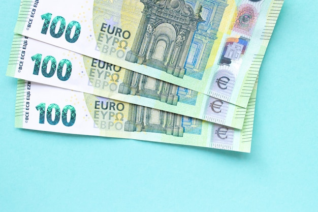 Three banknotes in denominations of 100 euros. they lie on top of each other in the form of a fan on a blue background. money and finance concept