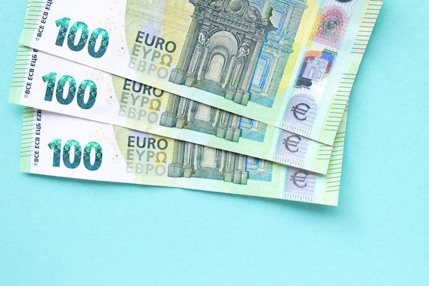 Три банкноты достоинством в 100 евро. они лежат друг на друге в виде веера на синем фоне. концепция денег и финансов