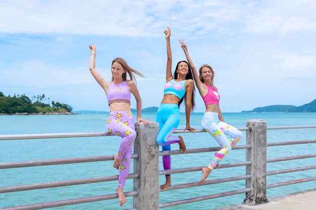 Three beauties are standing on the pier and posing in modern clothes for fitness.