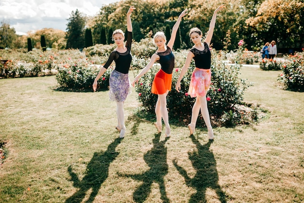Three beautiful ballerinas  dancing and balancing over sun light in summer park
