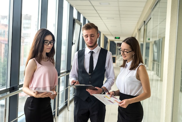 Three beautiful business partners discussing paperwork in modern    office hallway. meeting concept