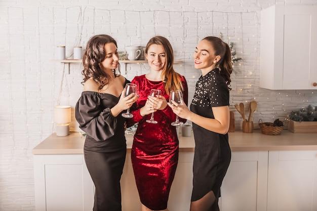 新年のキッチンの背景にあるクリスマスのダイニングテーブルでアルコールのガラスで笑っている3人の美しい陽気な幸せな若い女の子の友人