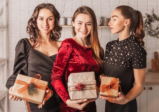 新年のキッチンの背景にあるクリスマスのダイニングテーブルで贈り物を笑っている3人の美しい陽気な幸せな若い女の子の友人