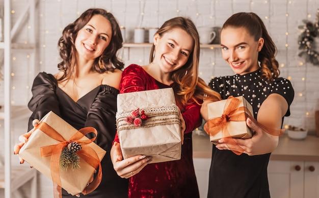 새해 부엌의 배경에 크리스마스 식탁에서 선물로 웃고 세 아름다운 쾌활한 행복 어린 여자 친구