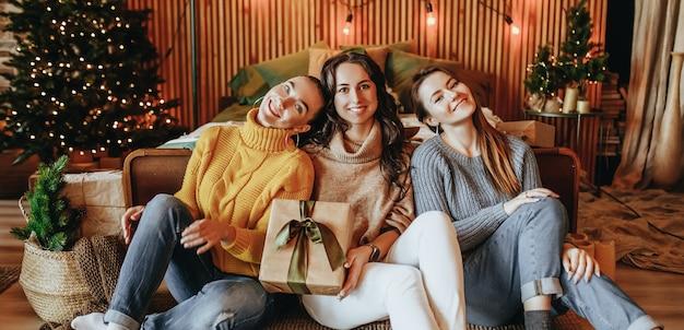 세 명의 아름답고 쾌활한 행복한 어린 여자 친구가 집에서 새해 나무 배경에 크리스마스 선물을 줍니다