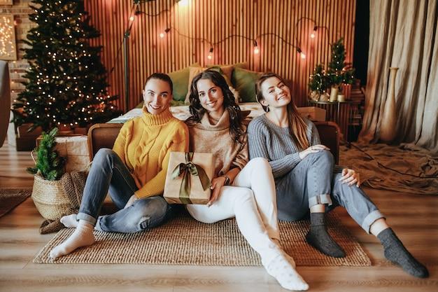 세 가지 아름 다운 쾌활 한 행복 한 젊은 여자 여자 친구 집에서 새해 나무의 배경에 크리스마스 선물을 제공