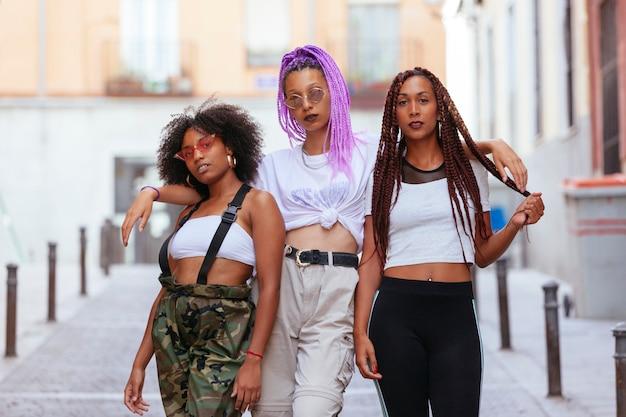 Three beautiful ethnic women walking down the street