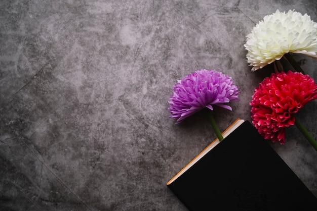 灰色のコンクリートの背景に閉じた本を持つ3つの美しい花