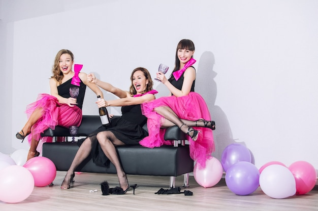 Three beautiful fun trendy women with beautiful makeup smile, laugh and celebrate with balloons