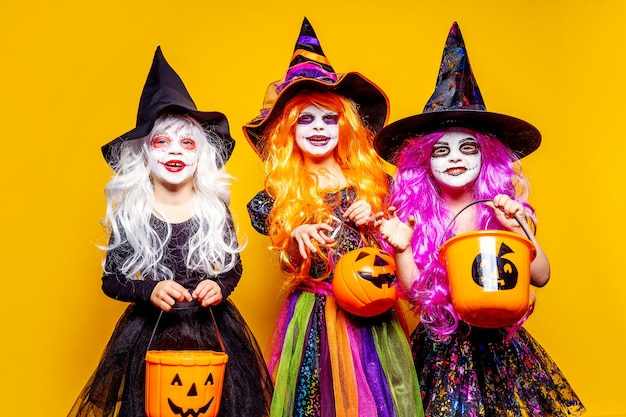 Three beautiful girl in a witch costume scaring and making faces