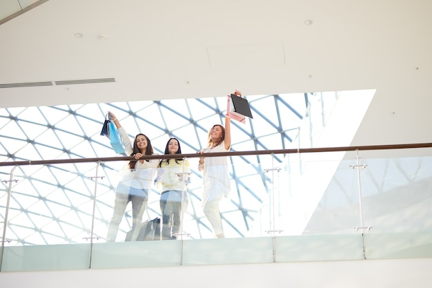 たくさんの買い物袋を持ったスタイリッシュなカジュアルな服を着た3人の美しい女の子がsの上に立っています