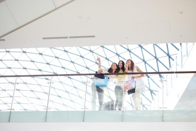 スタイリッシュなカジュアルな服を着た3人の美しい女の子がモールの2階に立っています。