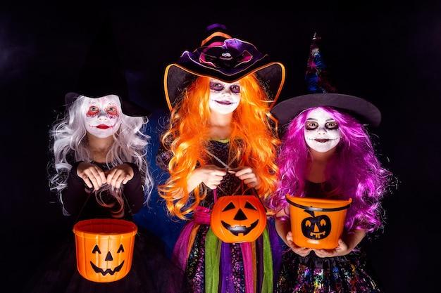 Три красивые девушки в костюме ведьмы на темном фоне в дыму.