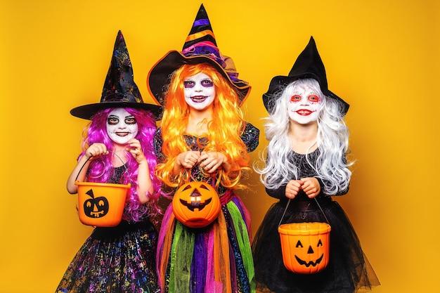 Три красивые девушки в костюмах ведьмы и шляпах на желтом фоне пугают и корчит рожи.
