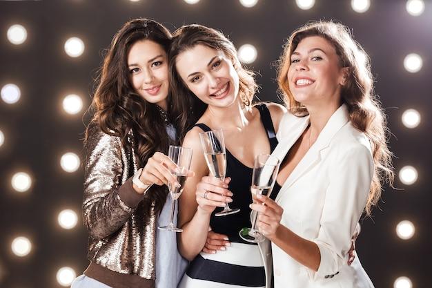 세련된 캐주얼 옷을 입은 세 명의 아름다운 소녀가 손에 샴페인 잔을 들고 조명으로 배경 벽에 미소를 짓고 있습니다. 파티 타임 .