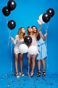 Три красивые девушки делают селфи на вечеринке над синей стеной