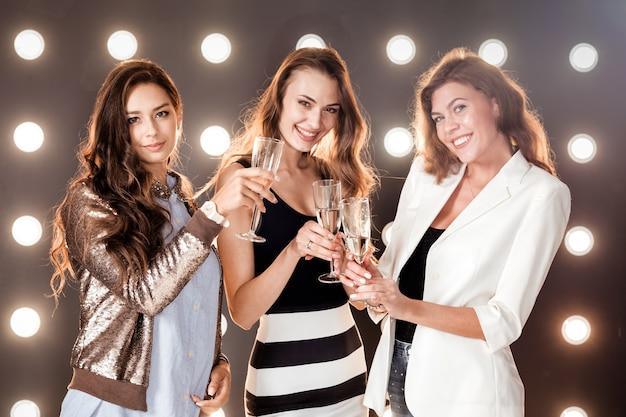 손에 샴페인 잔을 들고 조명이 있는 배경 벽에 웃고 있는 세 명의 아름다운 소녀. 파티 타임 .