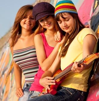 Three beautiful girls with guitar and graffiti wall