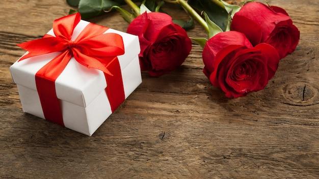 3つの美しい赤いバラが木の表面に横たわっています