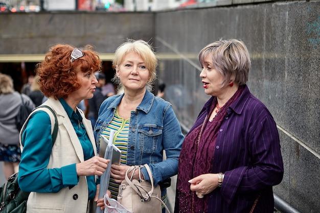 평상복을 입은 세 명의 아름다운 진지한 할머니가 낮에는 지하도 근처에서 이야기를 나누고 있습니다.