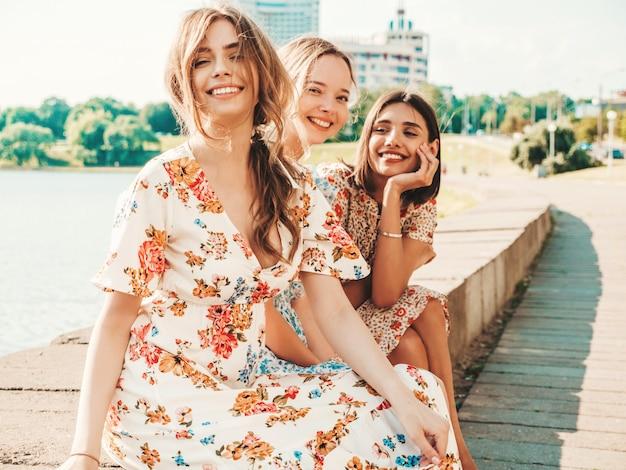 Три красивые улыбающиеся девушки в модном летнем сарафане позируют на улице