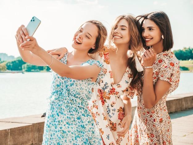 Selfieを取ってトレンディな夏のサンドレスで3つの美しい笑顔の女の子