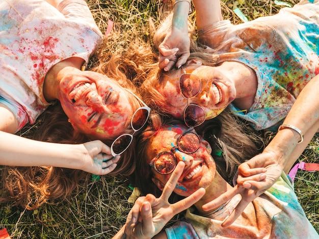 Три красивые улыбающиеся девушки позируют на вечеринке холи