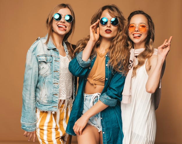 Three beautiful smiling girls in trendy summer casual clothes and sunglasses. sexy carefree women posing. positive models. showing tongue