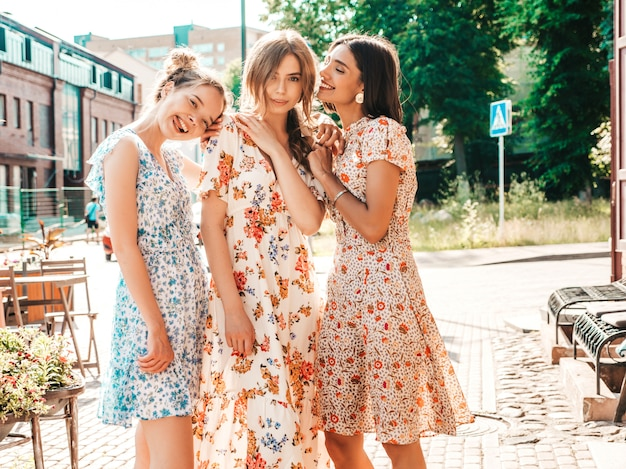 Three beautiful smiling girls in trendy summer sundress posing on the street
