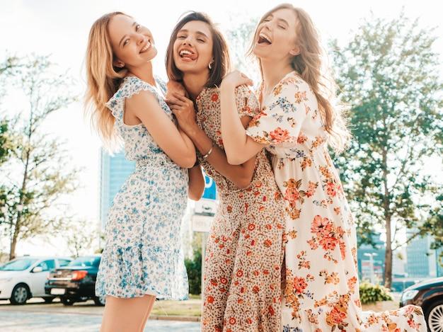 Three beautiful smiling girls in trendy summer sundress posing on the street