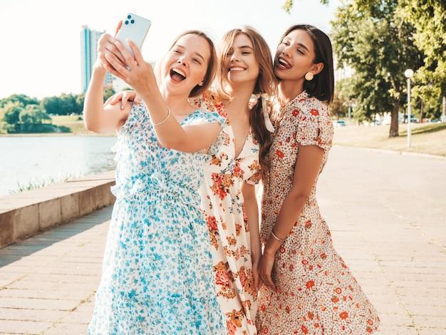 Three beautiful smiling girls in trendy summer sundress taking selfie