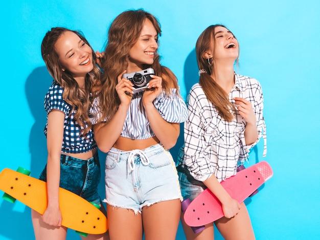 カラフルなペニースケートボードを持つ3つの美しいスタイリッシュな笑顔の女の子。夏の女性。レトロな写真カメラで写真を撮る